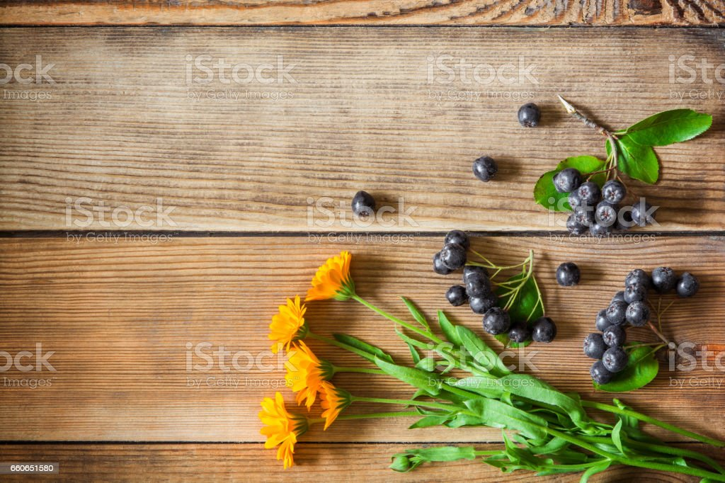 Calendula flowers and aronia berries (black chokeberry) on wooden background stock photo