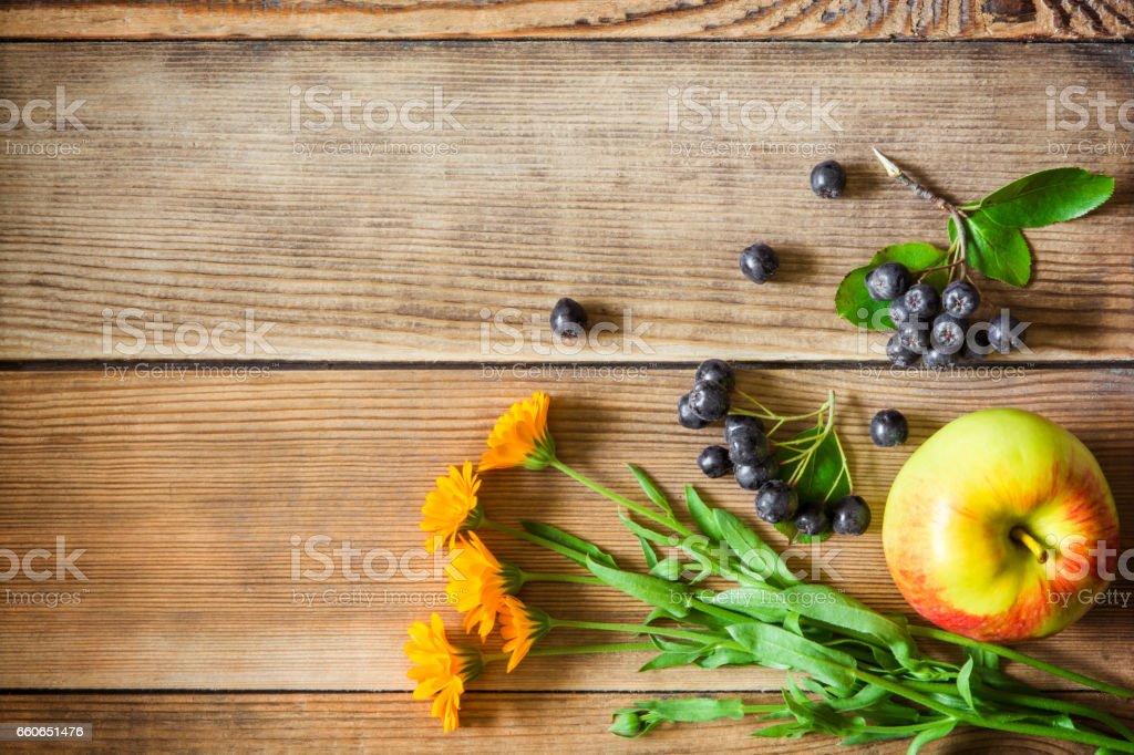 Calendula flowers, aronia berries (black chokeberry) and apple on wooden background stock photo