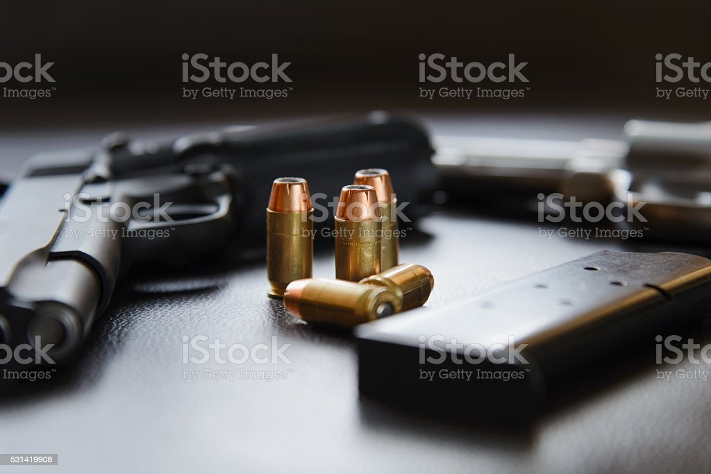 .45 Caliber hollow point bullets near handgun and magazine stock photo