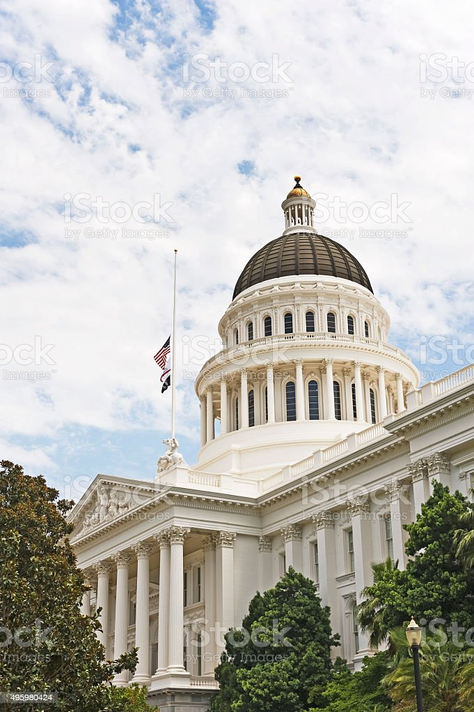 California Capitol with Flags Half Staff and Cloudy Sky stock photo