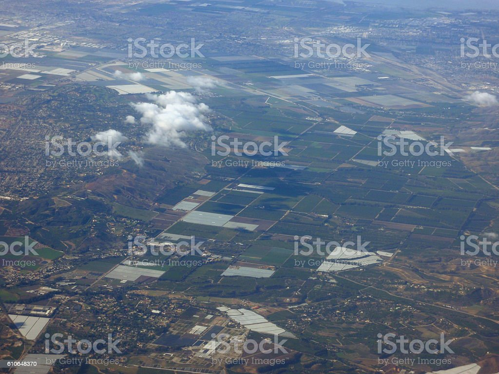 California fields of crops surrounded by suburbs, seen from above.