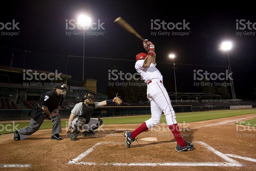 USA, California, San Bernardino, baseball players with batter swinging stock photo