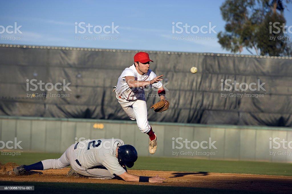 USA, California, San Bernardino, baseball runner sliding for base and baseman leaping for catch stock photo