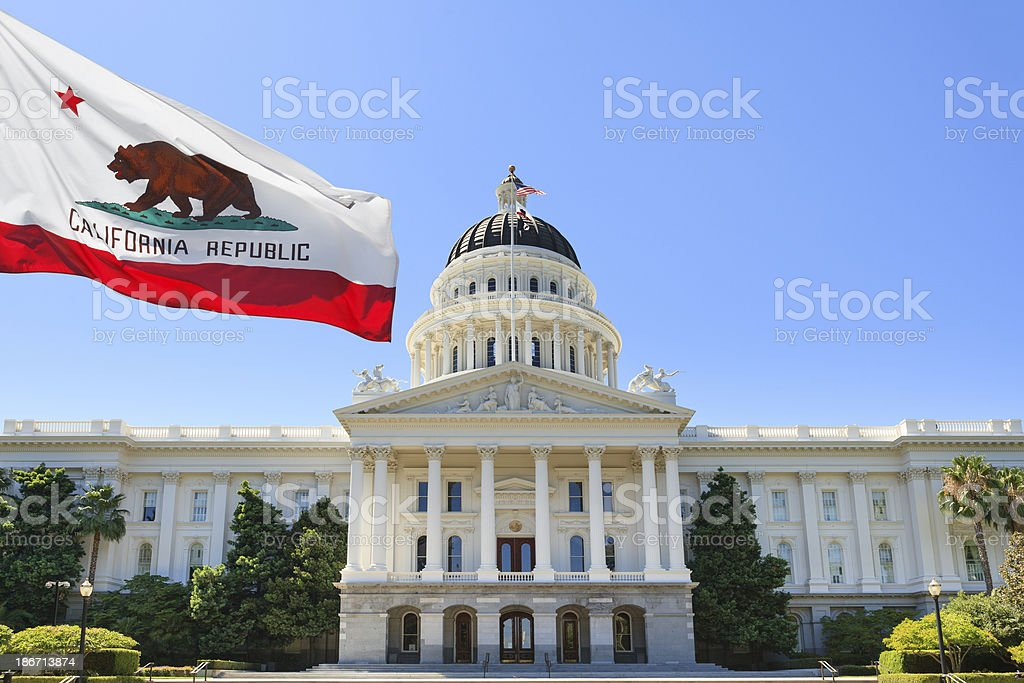 California state flag flying in front of capital building stock photo