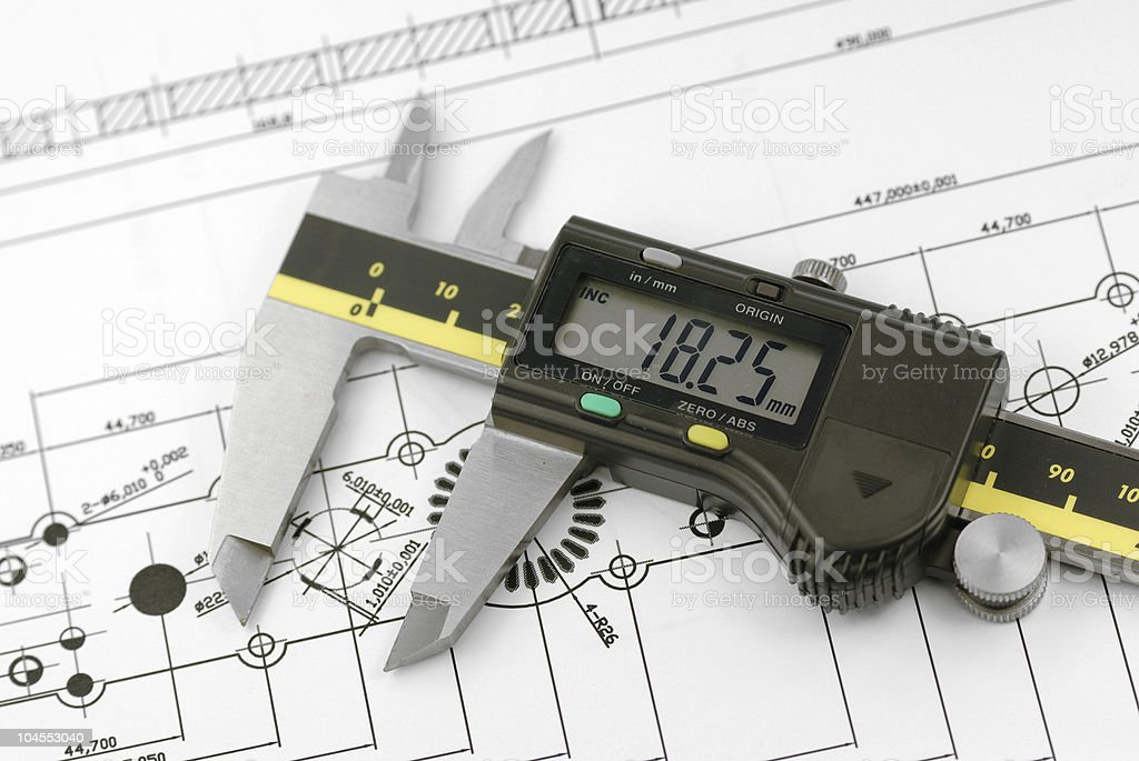 A caliper used to measure against a background of drawings stock photo