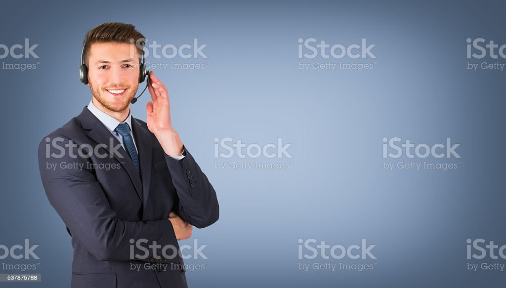 Call center employee during a telephone conversation on blue background stock photo