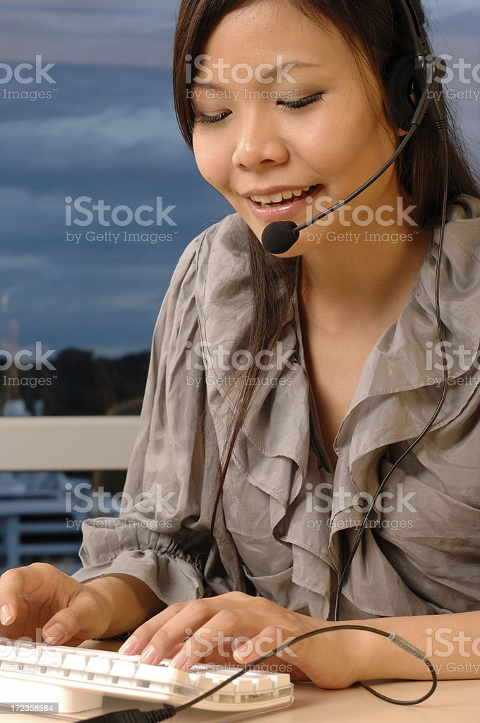 Call center service with a smile - Asian model royalty-free stock photo