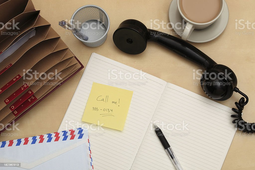 Call me note on a chaotic desk royalty-free stock photo