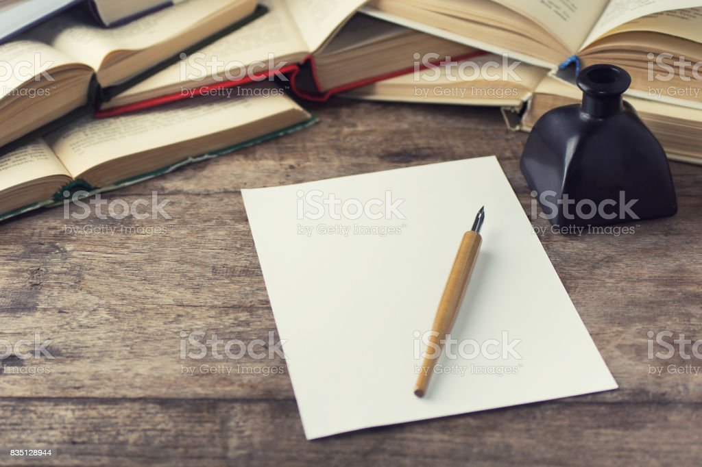 calligraphy dip pen and white paper on wooden table with books stock photo