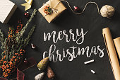 Calligraphy Merry Christmas text written blackboard with chalk, flat lay