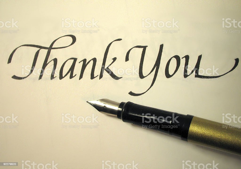 A calligraphy pen lying next to a paper that says Thank You  stock photo