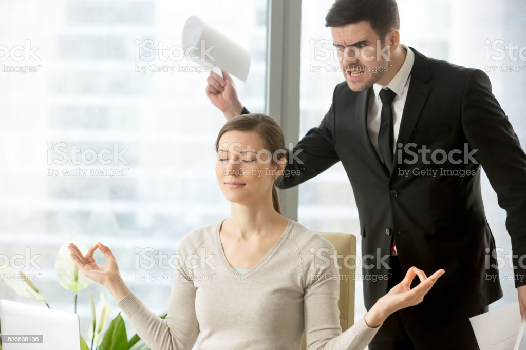 Calm attractive businesswoman meditating in office, ignoring angry bad boss stock photo