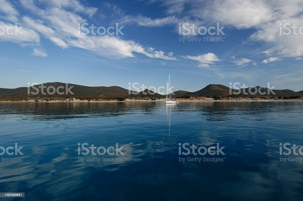 calm bay with a sail boat in south sardinia royalty-free stock photo