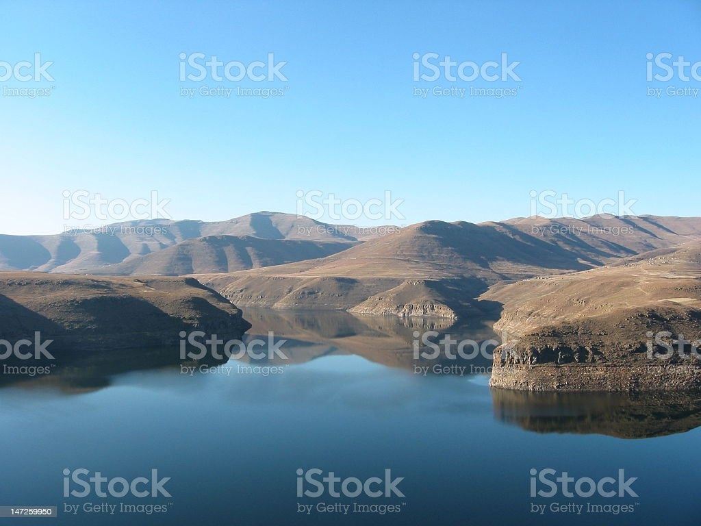 Calm body of water surrounded by little islands at Lesotho stock photo