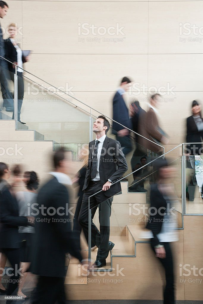 Calm businessman in busy office staircase stock photo