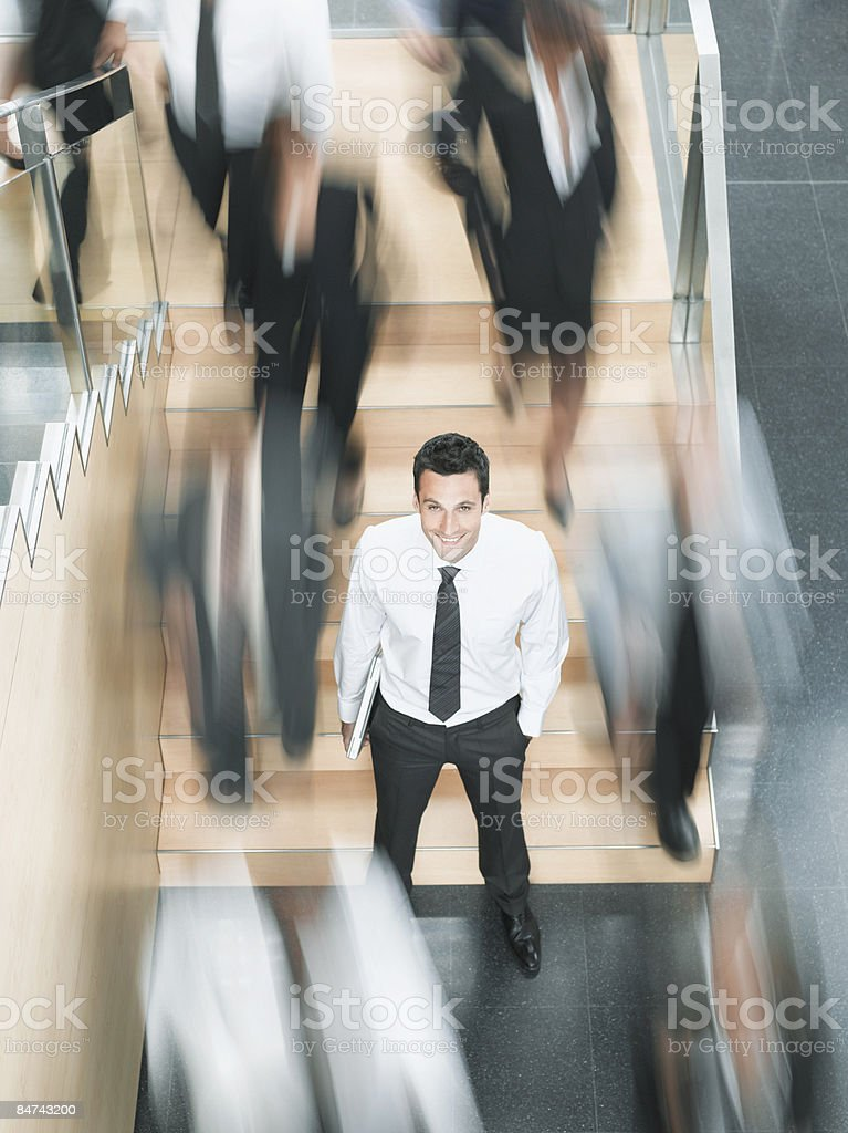 Calm businessman standing in busy office stock photo