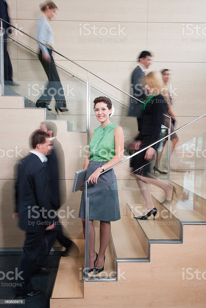 Calm businesswoman in busy office staircase stock photo