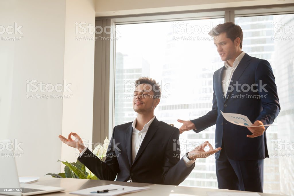 Calm employee meditating at workplace, angry boss shouting, stress management stock photo