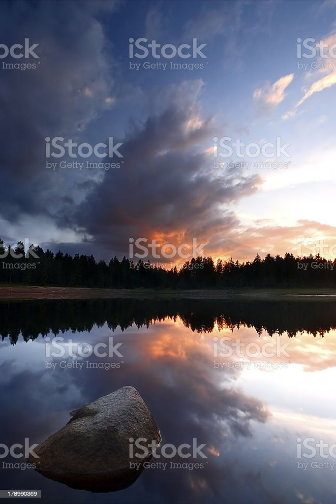 calm lake at sunset with rock royalty-free stock photo