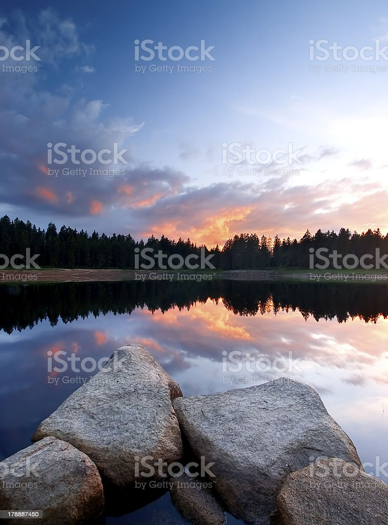 calm lake at sunset with rocks royalty-free stock photo