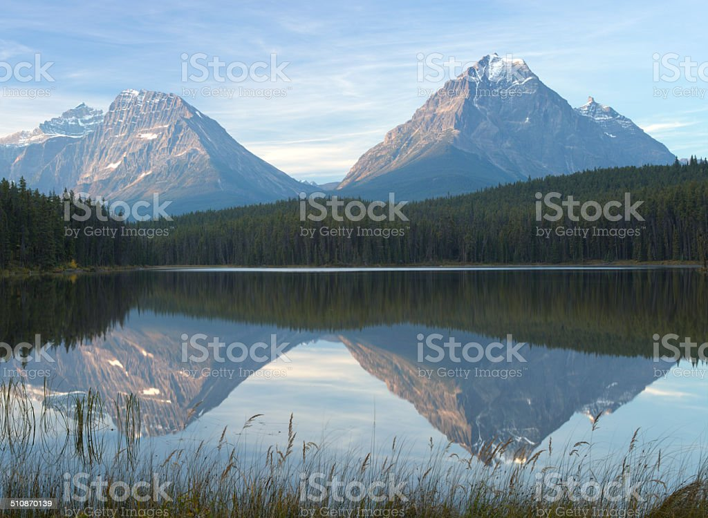 Calm Leech lake in the Canadian Rockies with mountains, trees stock photo