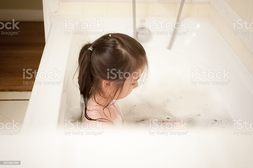 Calm little girl taking bubble bath with a bath toy stock photo