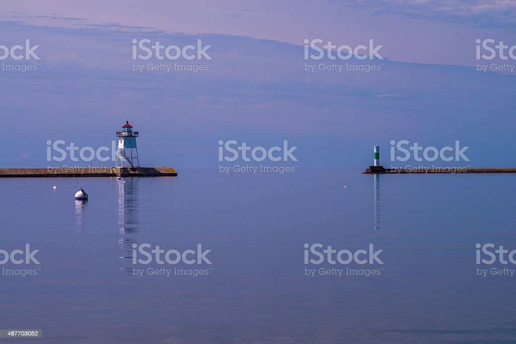 calm morning waters, grand marais lighthouse stock photo