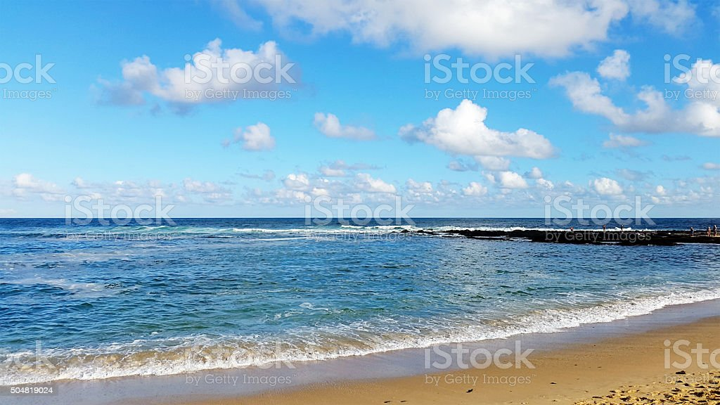 Calm ocean seen from water's edge with light cloud background stock photo
