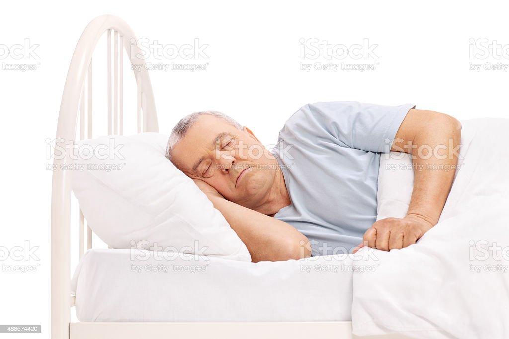 Calm senior man sleeping in a bed stock photo