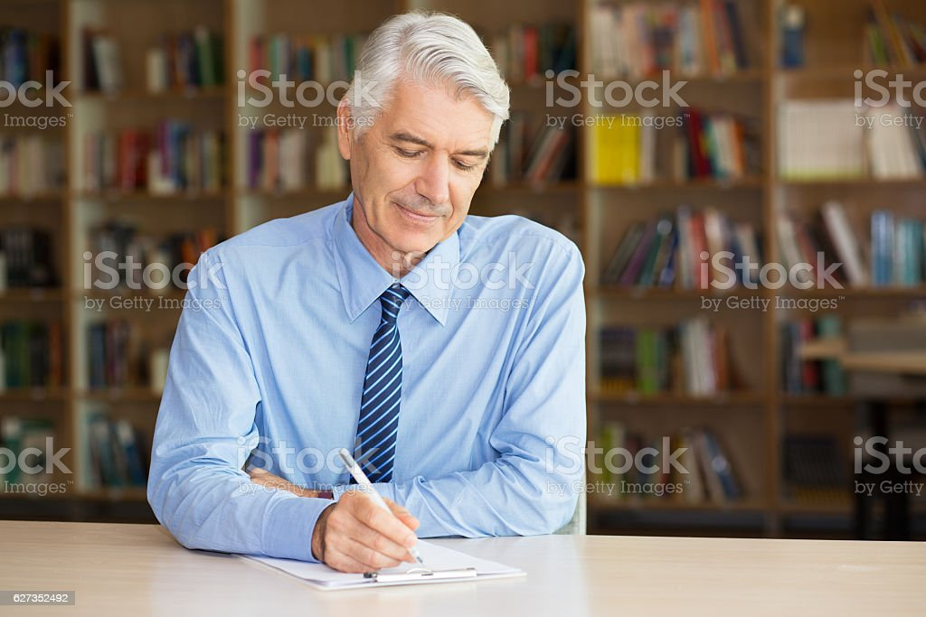 Calm senior man writing on paper in library stock photo