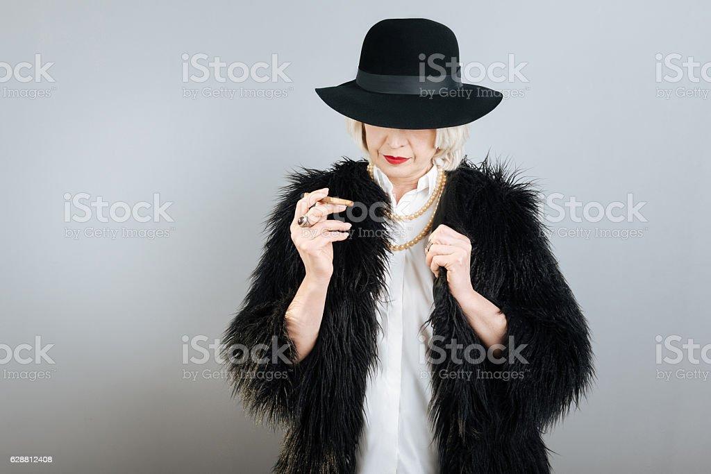 Calm senior woman holding cigarette . stock photo