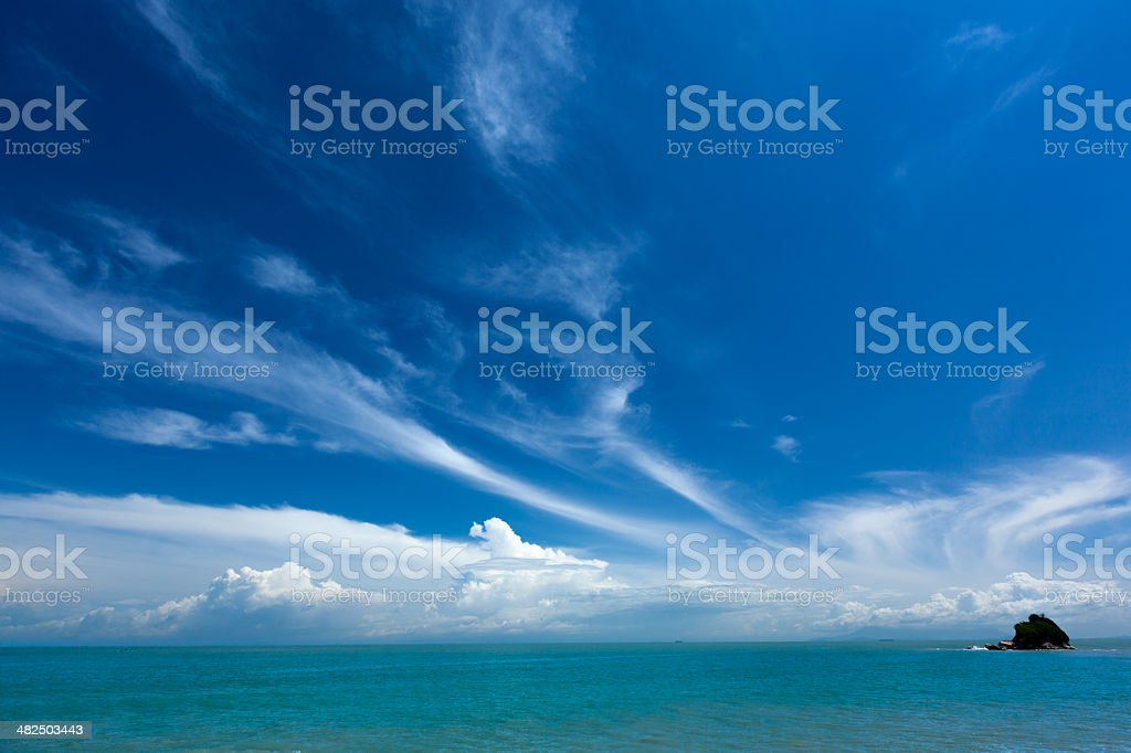 Calm turquoise sea and wispy blue sky stock photo