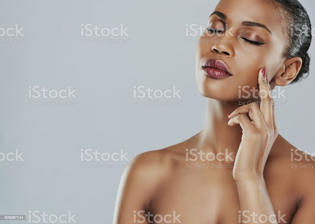 Calm woman with closed eyes and touching cheek stock photo