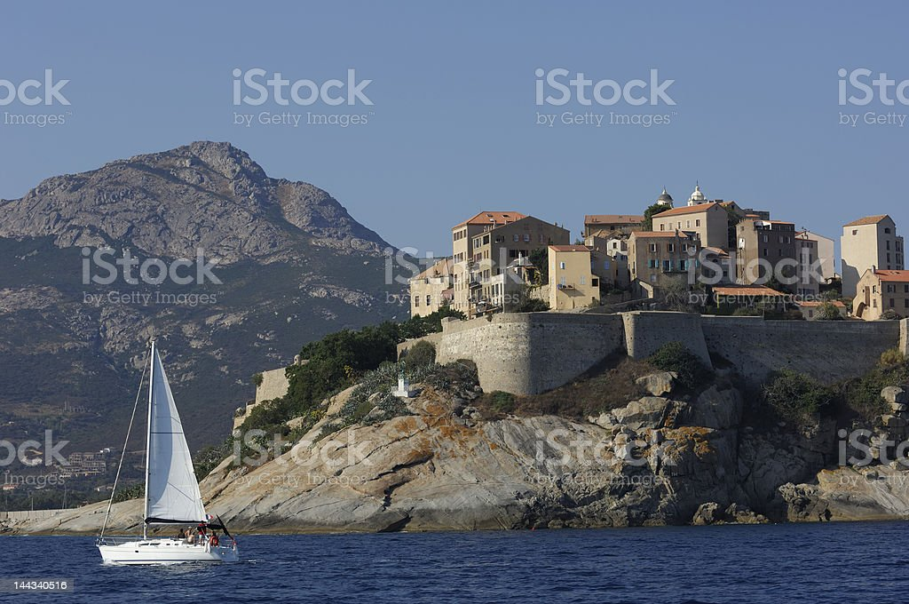 Calvi village on the sea with sailing boat royalty-free stock photo