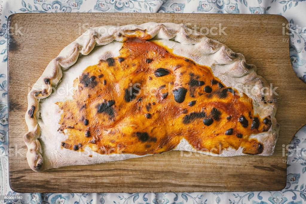 Calzone on the wooden board top view stock photo