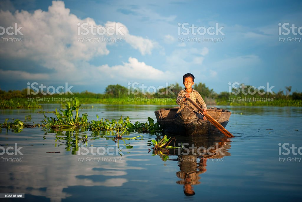 Cambodian boy travelling by boat in his floating village Cambodia. royalty-free stock photo