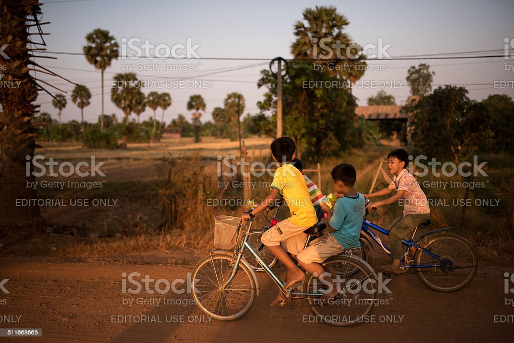 Cambodian children cycling at sunset stock photo