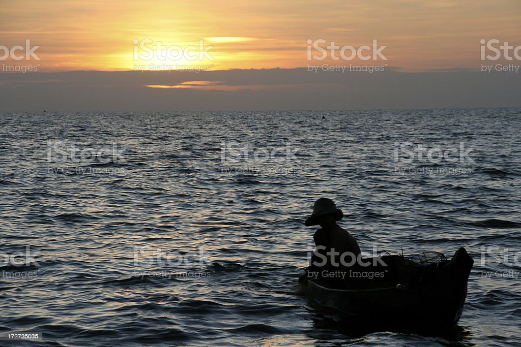 Cambodian Fisherman Silhouetted By Setting Sun on Tonle Sap Lake royalty-free stock photo
