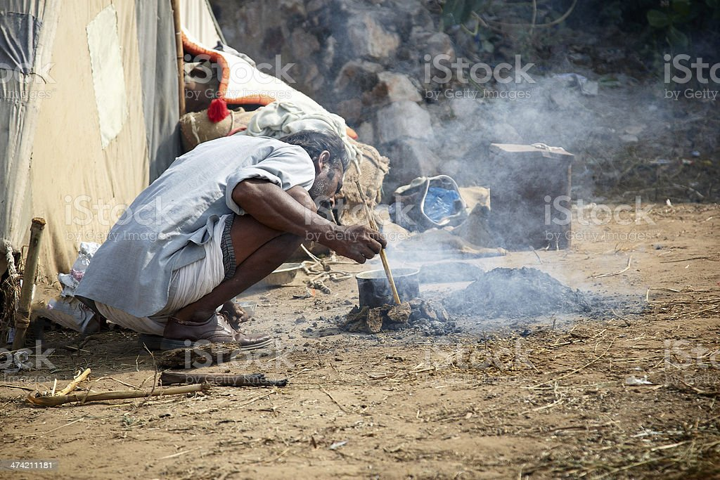 Camel herder cooking over an open wood fire stock photo