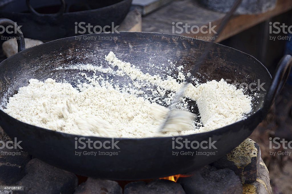 Camel herder roasting coconut in pan over open wood fire stock photo