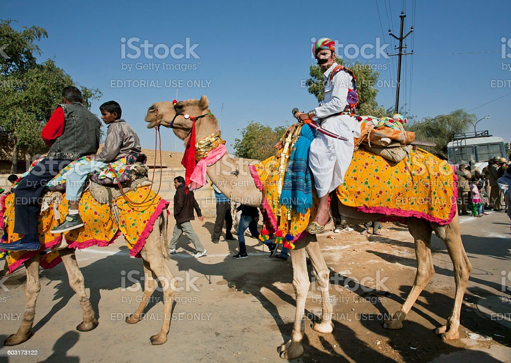 Camel rider in colorful dress goes on popular Desert Festival stock photo