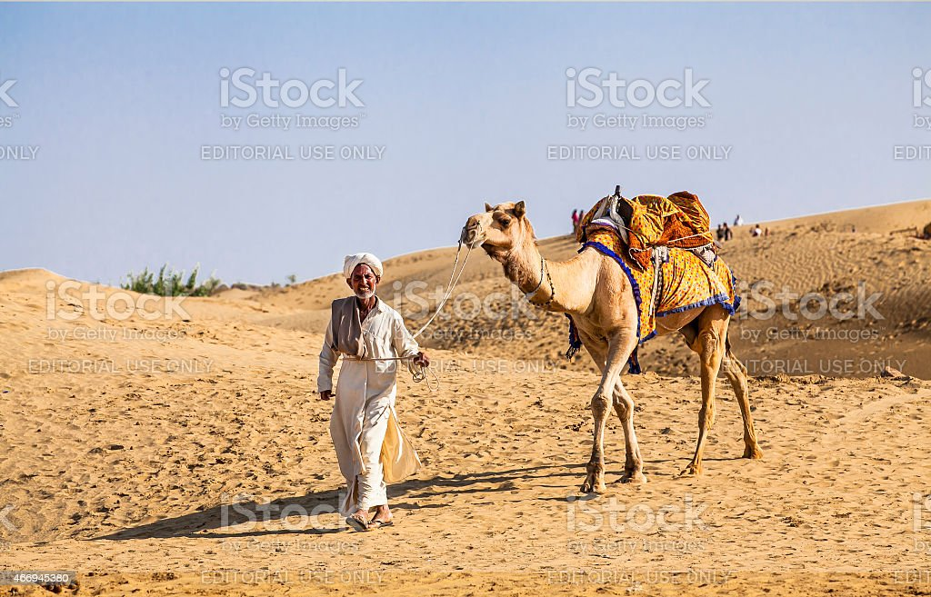 Camel riding activity for tourists is income for desert villagers . stock photo