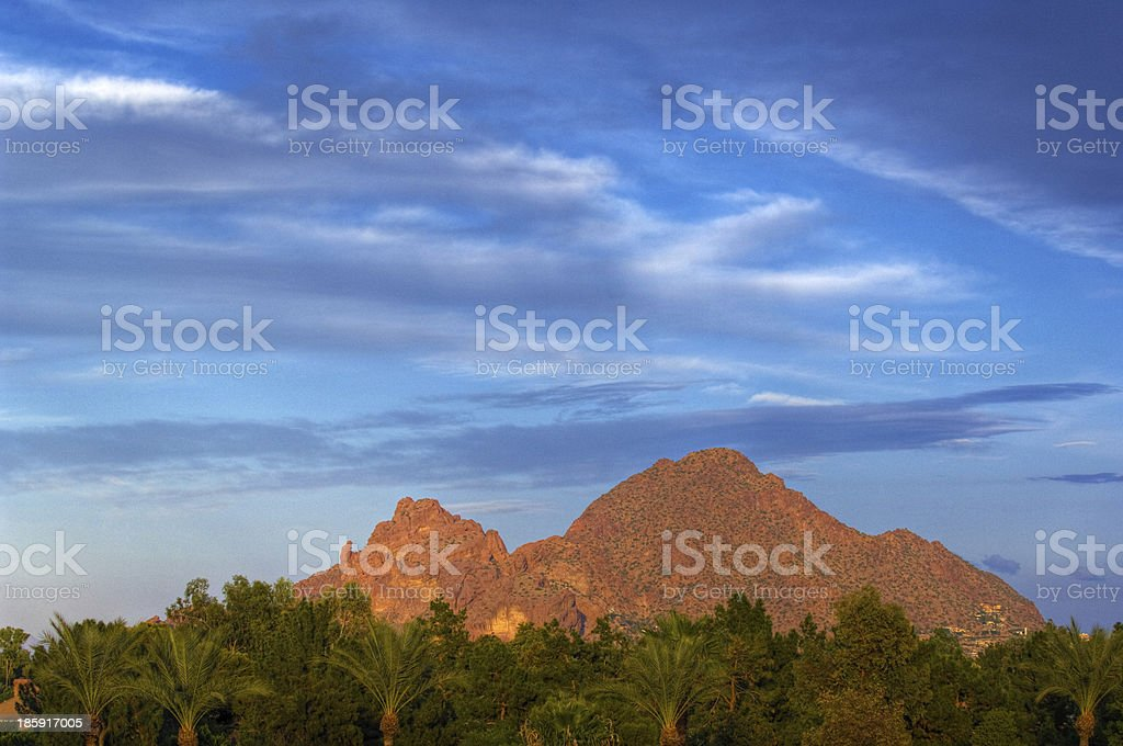 Camelback Mountain towering over trees in the distance stock photo