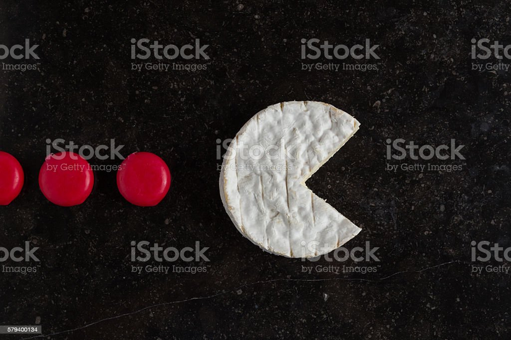 Camembert cheese and mini pieces on black background stock photo