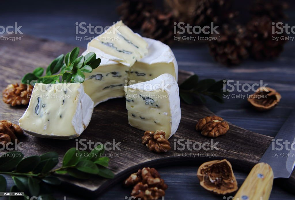 camembert cheese with a blue mold and walnut stock photo