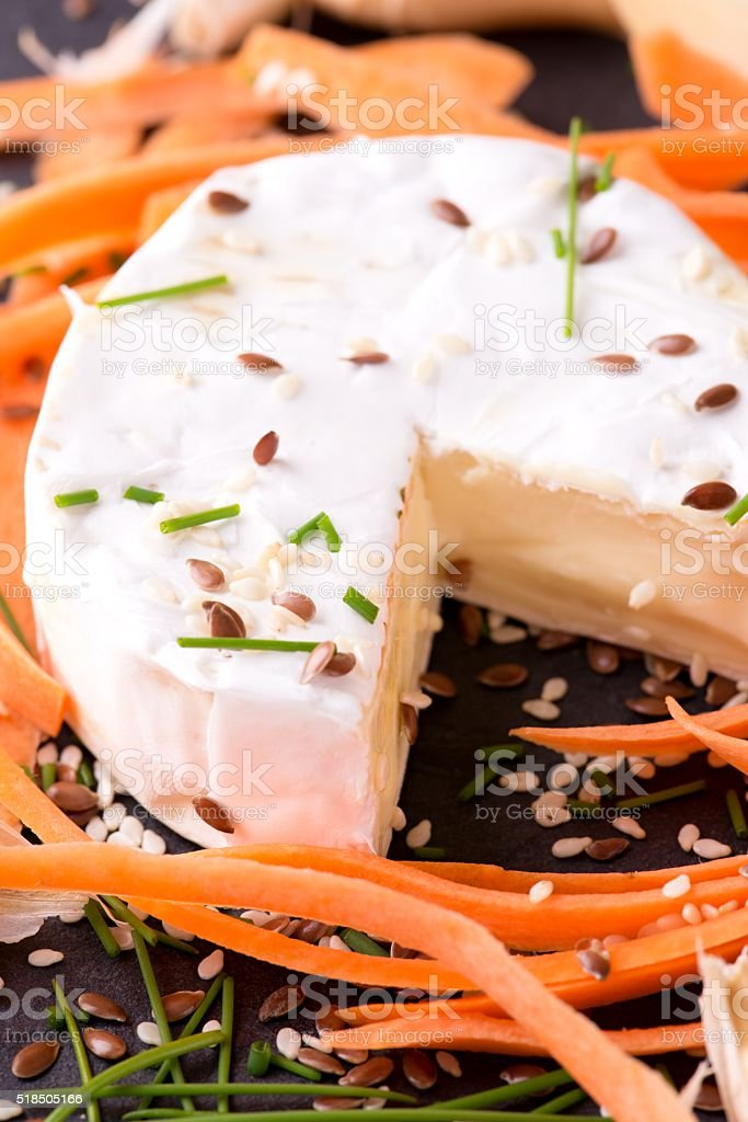 Camembert cheese with chive and carrot around stock photo