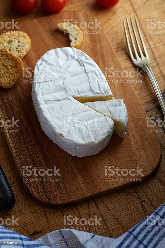 Camembert on wooden cutting board stock photo
