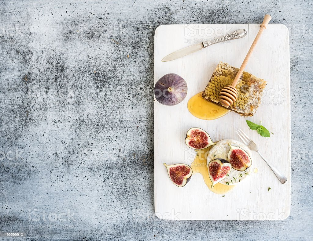 Camembert or brie cheese with fresh figs, honeycomb and glass stock photo