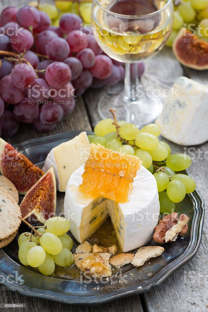 camembert with honey and fruit, snacks and wine on a plate, vertical,...