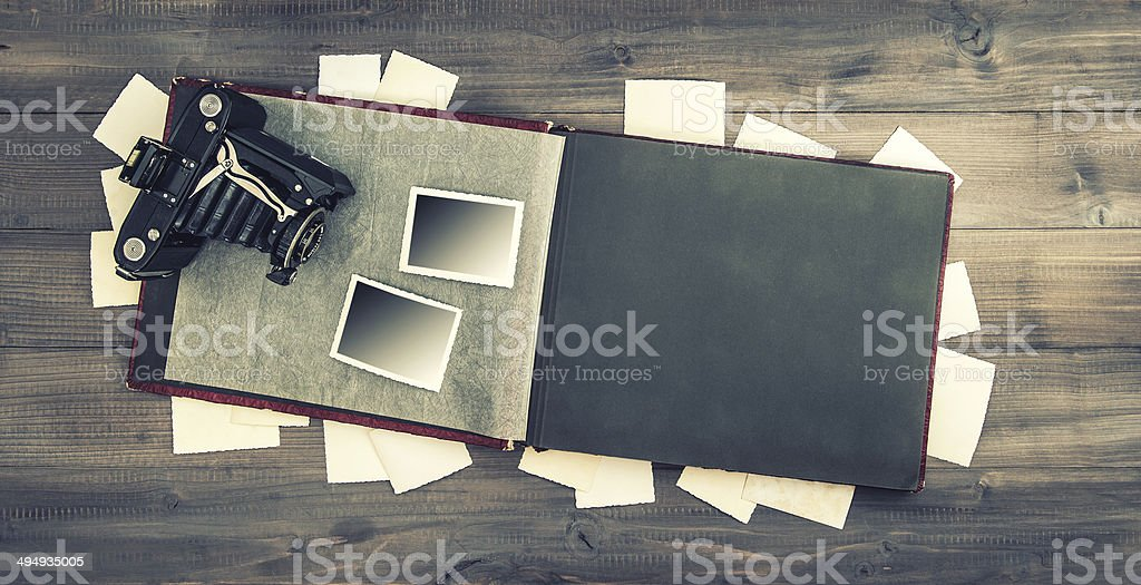 camera and album with old photos on wooden table stock photo